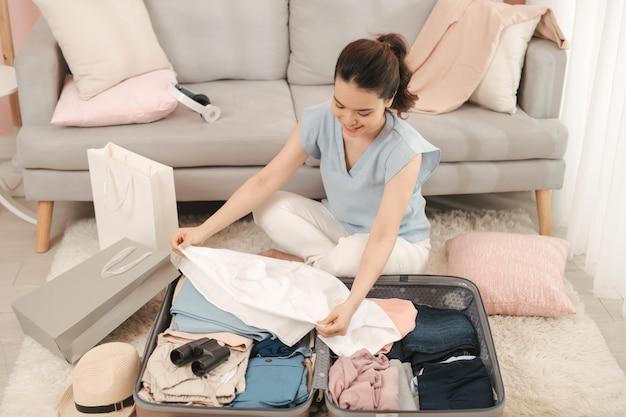 陽気な女性のパッキングスーツケースと旅行の準備