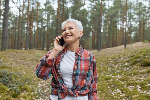 Allegro pensionato femmina con corti capelli biondi in posa nella natura selvaggia con alberi di pino sullo sfondo, godendo della freschezza, condividendo impressioni con un amico, parlando al cellulare, ridendo