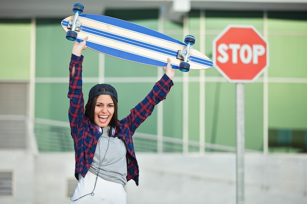Cheerful female posing with longboard