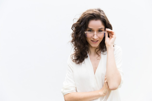 Cheerful female professional adjusting glasses