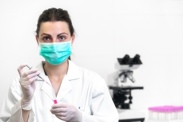 Cheerful female scientist with protective mask posing at the laboratory.