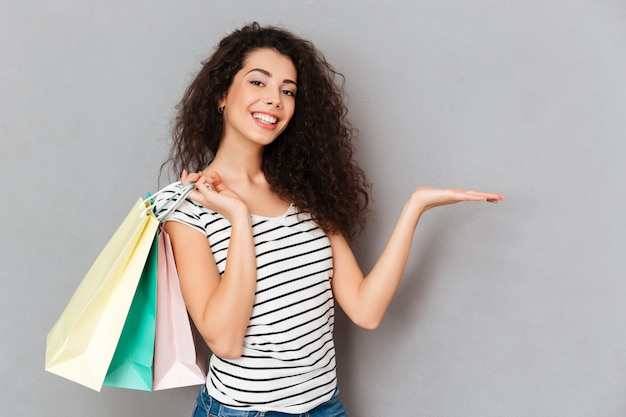 Cheerful female shopaholic being excited with all purchases and packs after shopping demonstrating product on her palm copy space