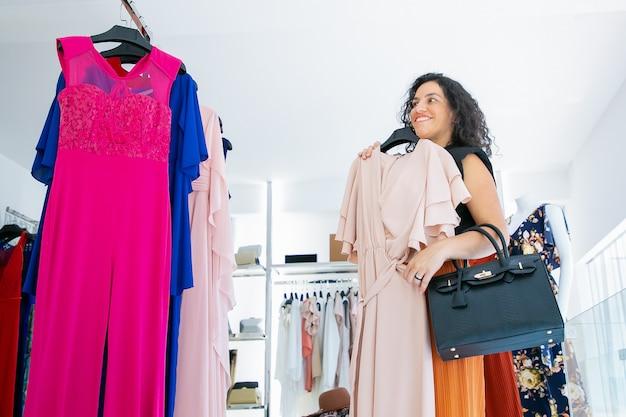 Веселая женщина-покупательница, применяя платье с вешалкой и глядя в зеркало. женщина выбирает одежду в магазине модной одежды. шоппинг или розничная концепция