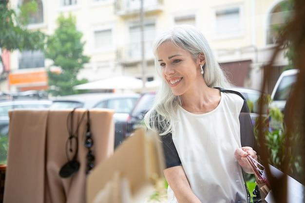 Веселая женщина-покупательница, глядя на аксессуары в витрине магазина, держа сумки, стоя в магазине снаружи. вид спереди через стекло. концепция магазина окон