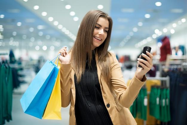 휴대 전화에 쾌활 한 여성 구매자 문자 메시지