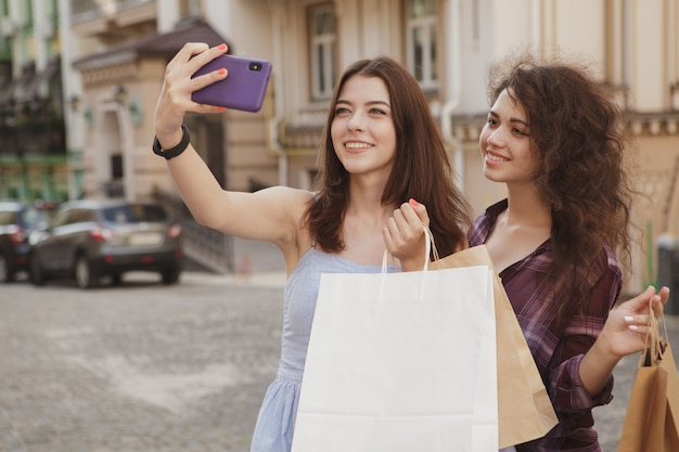 Cheerful female shoppers using smart phone, taking photos after shopping