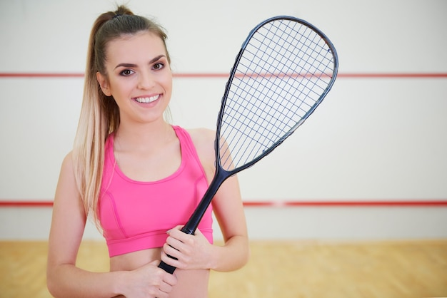Веселый женский игрок в сквош с ракеткой