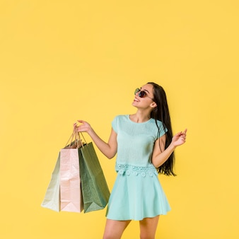 Cheerful female standing with shopping bags
