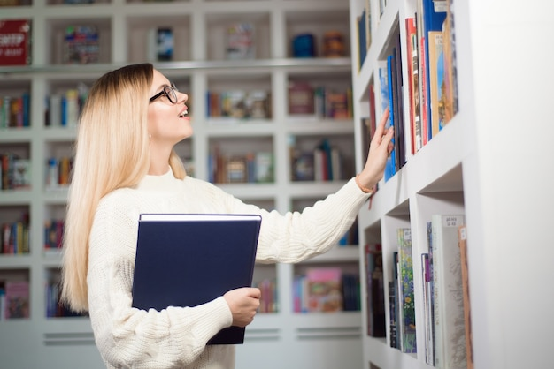수업 사이 휴식 시간에 대학의 현대적인 인테리어 도서관 책장 근처에 서 있는 안경을 쓴 쾌활한 여학생