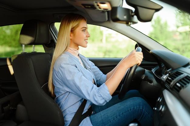 Веселая студентка в машине, урок в автошколе. мужчина учит леди водить автомобиль. образование водительского удостоверения