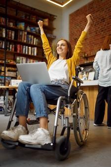 Веселая студентка в инвалидной коляске, инвалидности, книжной полке и интерьере университетской библиотеки на фоне. молодая женщина-инвалид, обучающаяся в колледже, инвалиды или парализованные люди получают знания