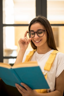 Cheerful female student reading book in eyeglasses
