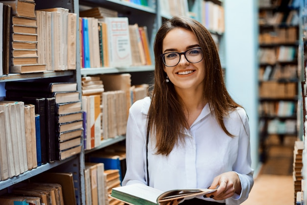 도서관에서 손에 책을 가진 쾌활 한 여자 학생