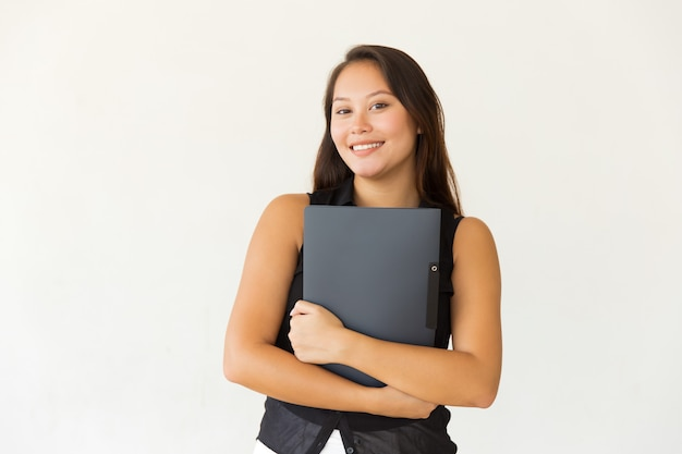 Cheerful female student with folder smiling at camera