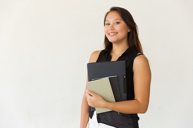 Cheerful female student with folder and textbooks