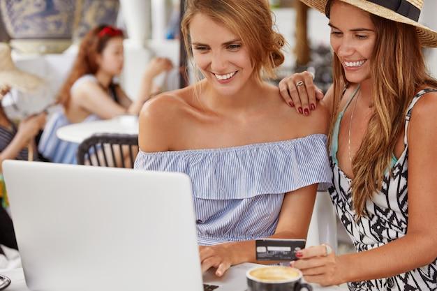 쾌활한 여학생은 랩톱 컴퓨터에서 프로젝트를 확인합니다. 웃는 동성애 여성은 인터넷 웹 스토어를 서핑하고, 온라인 지불을 위해 신용 카드를 들고, 현대 전자 장치를 사용합니다. 온라인 쇼핑.
