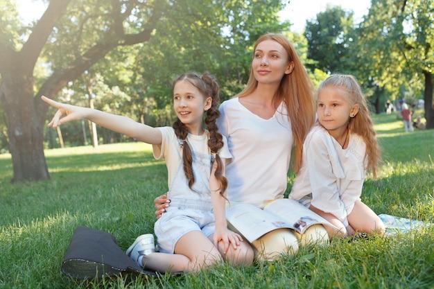 Веселая учительница отдыхает в парке на траве со своими учениками двумя школьницами