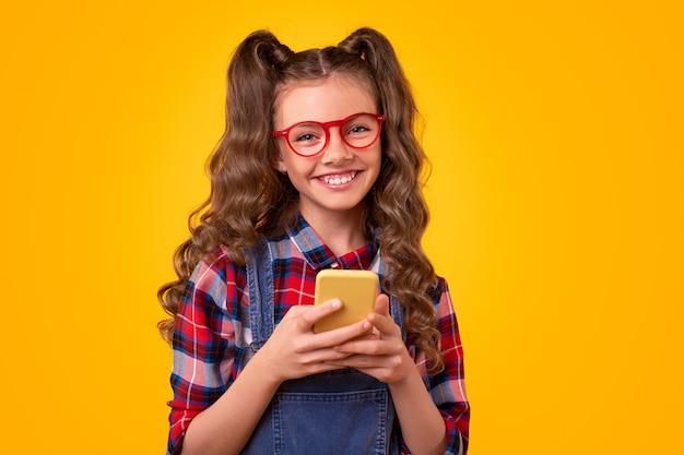 Веселая девушка-подросток в повседневной одежде и очках смотрит во время использования мобильного приложения на смартфоне