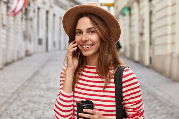 쾌활한 여성 관광객은 도시 공간에서 포즈를 취하고 종이 컵에 테이크 아웃 커피를 마신다.