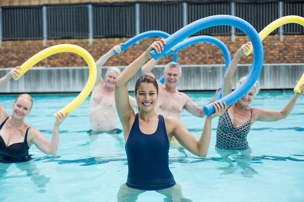 Cheerful female trainer and senior swimmers exercising with pool noodle