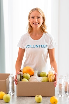 Cheerful female volunteer holding box with food for donation