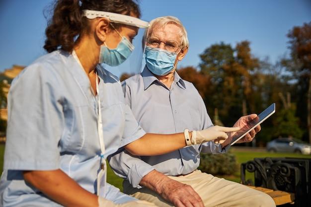 노인과 함께 벤치에 앉아 의료 마스크를 쓴 쾌활한 여성