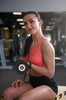 Cheerful female weightlifter exercising with dumbbells at the gym