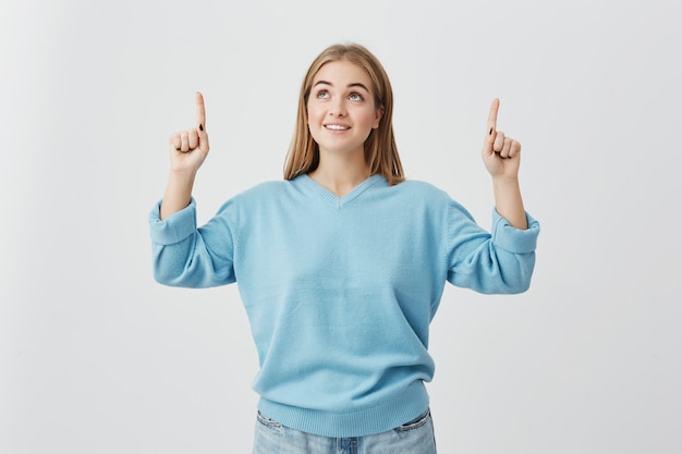 Cheerful female with fair hair, wearing blue sweater and jeans, pointing upwards with her fingers being pleased to see something. blonde-haired girl joyfully smiling with teeth