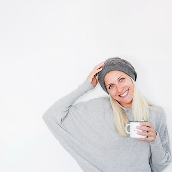 Cheerful female with hot drink touching hat