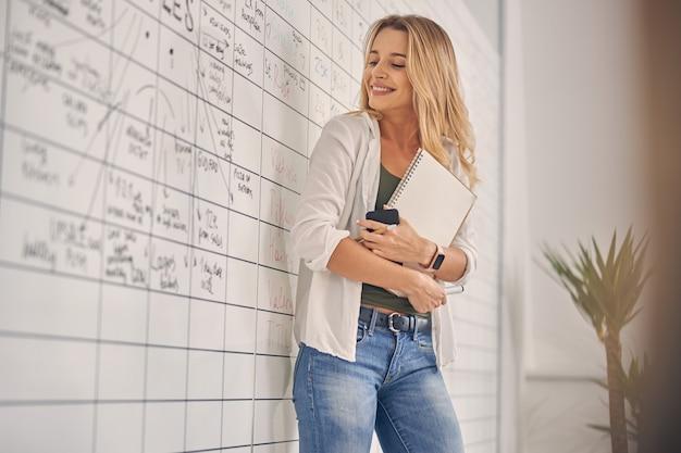 Веселая работница смотрит на доску планировщика и улыбается, держа в руках альбом для рисования и смартфон