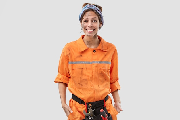 Cheerful female worker posing against the white wall