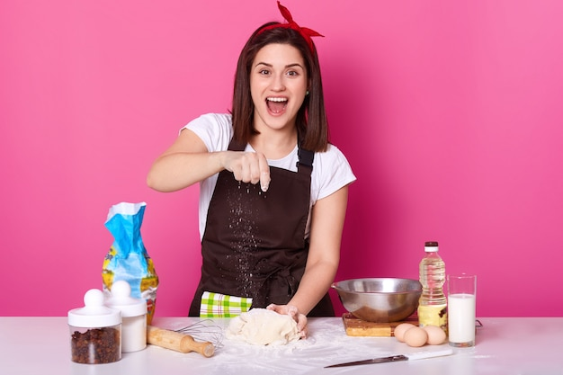 Cheerful female works in kitchen, wants to prepare homemade pastry, happily sprinkles flour on dough, lokks at camera with wide open mouth. housekeeper wears casual t shirt, brown apron and hair band.