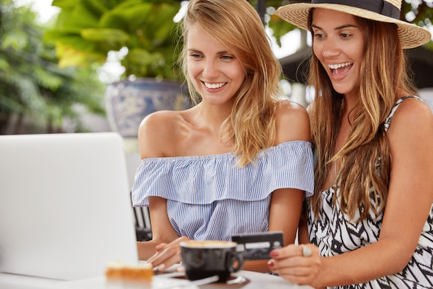 Cheerful females friends dressed in summer clothes, pay with credit card online, make orders via internet, connected to free wifi. happy young women make transactions on modern laptop computer