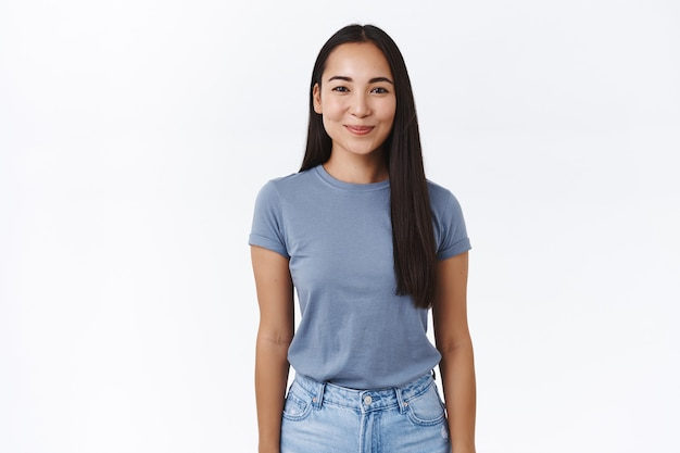 Веселая, женственная и глупая молодая азиатская девушка улыбается счастливой, смотрит в камеру с восхищением и радостью, стоя в непринужденной позе с опущенными руками, позирует над белой стеной, студийный портрет
