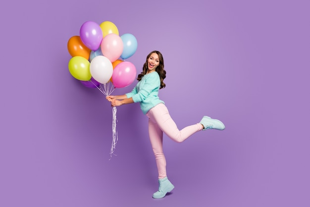 Cheerful feminine girl hold many baloons enjoy festive woman day event scream wear turquoise pastel sweater pink footwear.