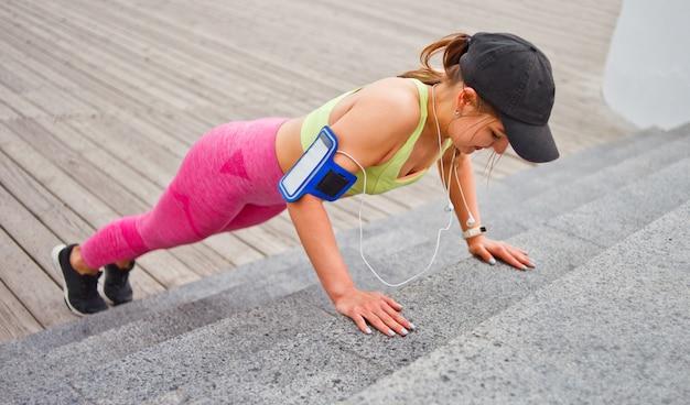 スポーツウェアと屋外階段から腕立て伏せを行うキャップで陽気なフィット女性。