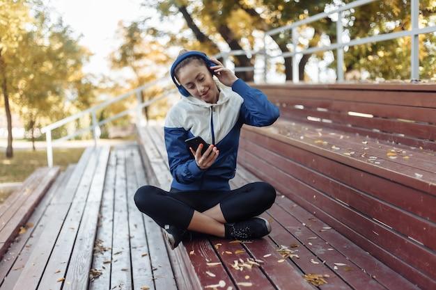나무 스탠드에 앉아서 헤드폰에서 음악을 듣고 운동복에 쾌활 한 맞는 여자.