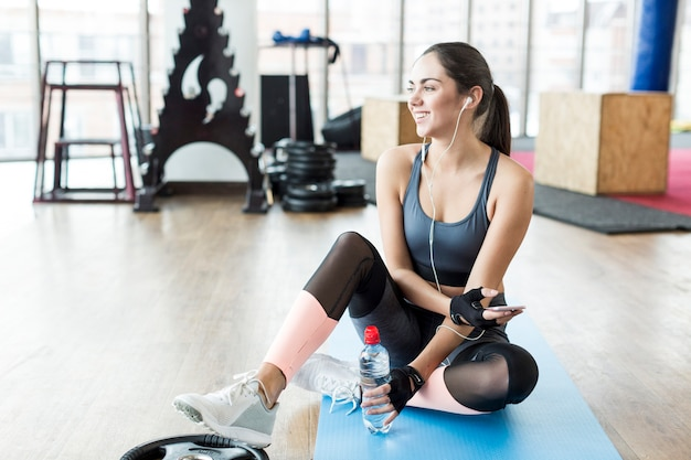 Cheerful fit woman listening to music