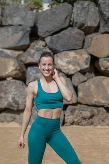Cheerful fit woman touching neck