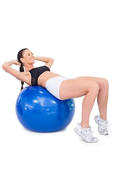 Cheerful fit woman working out with exercise ball
