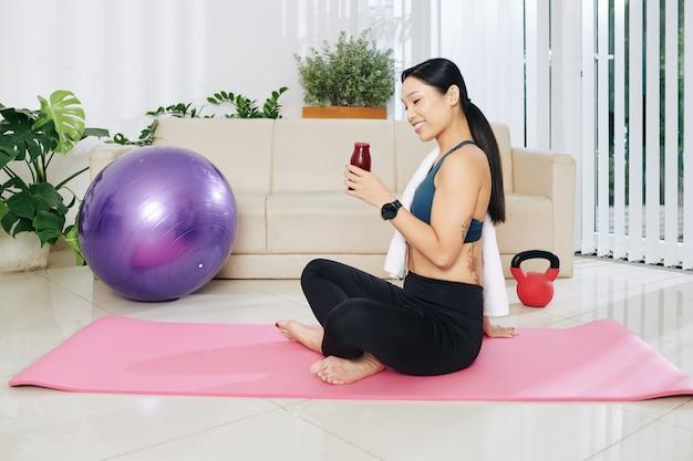 Жизнерадостная молодая вьетнамская женщина сидит на коврике для йоги и пьет ягодный смузи после тренировки дома