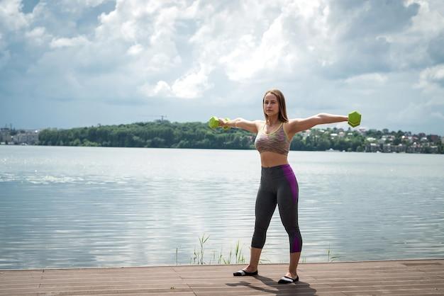 屋外で、ダンベルで運動するスポーツウェアの陽気なフィットネス女性。健康的な生活様式