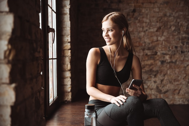 Cheerful fitness woman sitting in gym and listening music