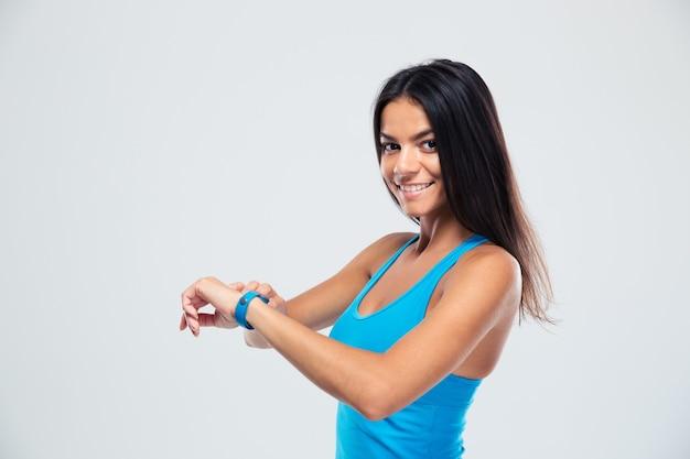 Веселая фитнес-женщина с помощью фитнес-трекера