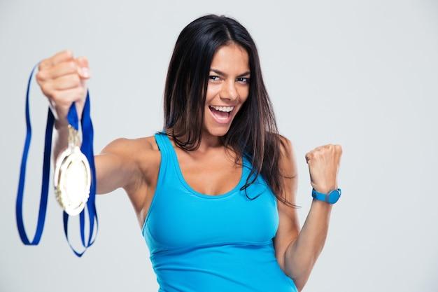 メダルを持つ陽気なフィットネス女性