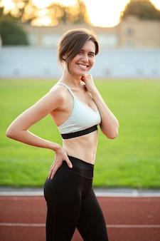 完璧なボディを持つ陽気なフィットネス女性は草の近くでポーズをとるファッショナブルなスポーツウェアを着ています Premium写真