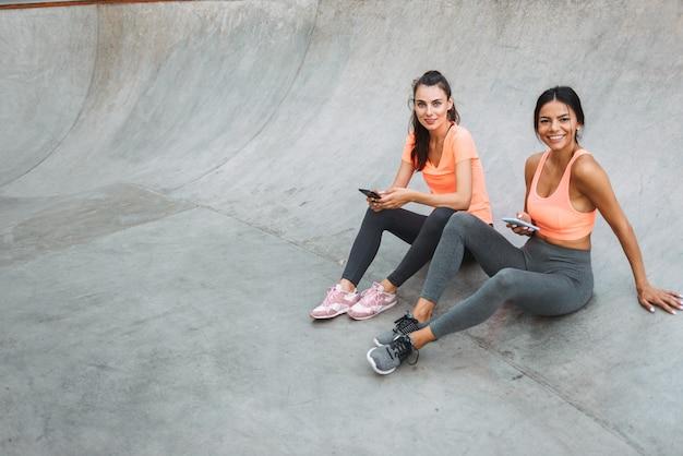 콘크리트 운동장에 앉아있는 동안 미소하고 핸드폰을 함께 들고 운동복에 쾌활한 피트니스 여성