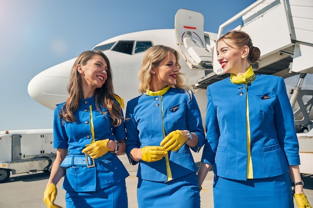 Cheerful flight attendants standing in front of the landed large civil aircraft