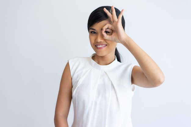 Cheerful flirty girl showing ok sign