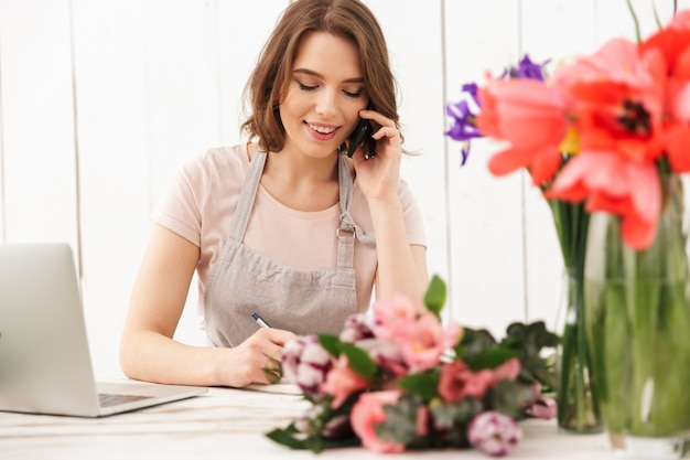 Cheerful florist lady over flowers in workshop